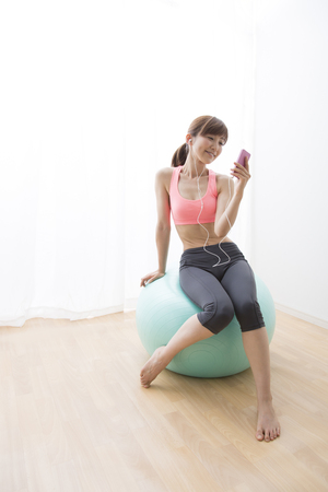 balance ball: Woman listening to music on a balance ball Stock Photo
