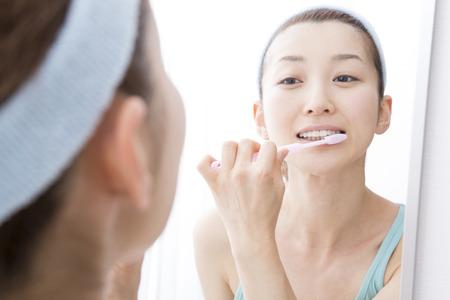 Mulher escovando os dentes na frente do espelho