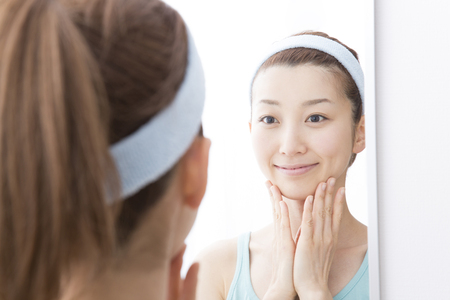 Woman to check your skin in the mirror Standard-Bild