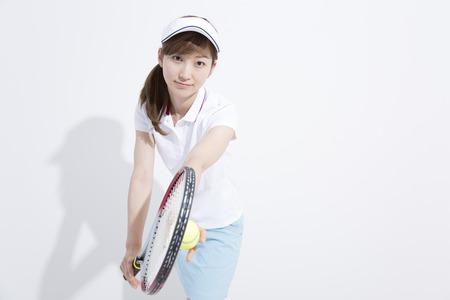 salud y deporte: La mujer a la postura del servicio del tenis