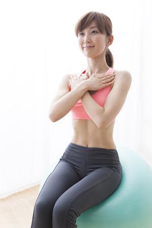 バランス ボールに乗って女性 写真素材