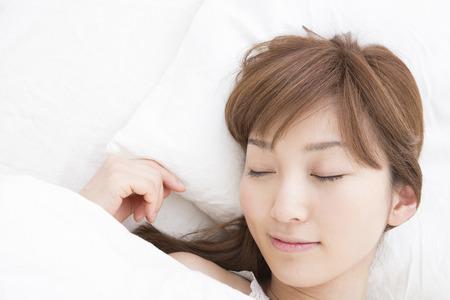 ベッドで寝ている女性 写真素材