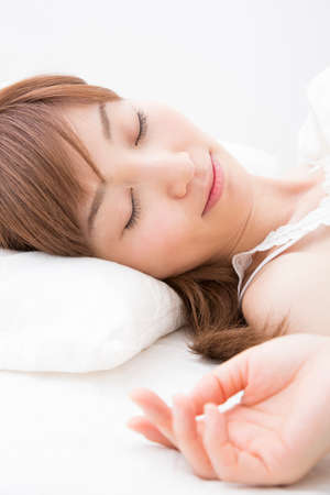 early 30s: Woman sleeping in a bed Stock Photo