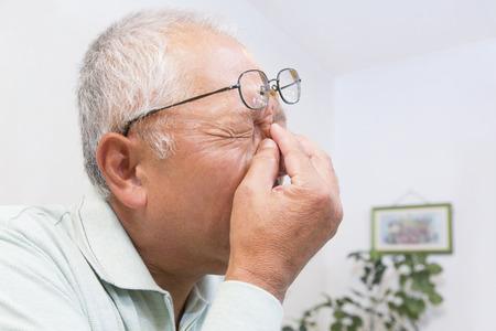 目の内側の隅を押すと年配の男性 写真素材