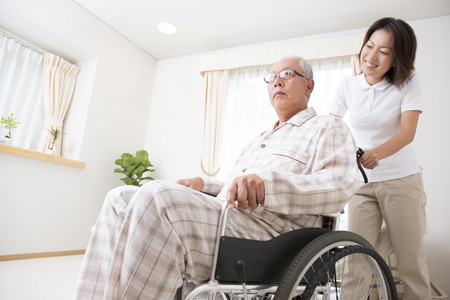 asian hospital: Caregiver to put the senior man in wheelchair