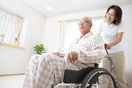 persona en silla de ruedas: Cuidador para poner el hombre mayor en silla de ruedas