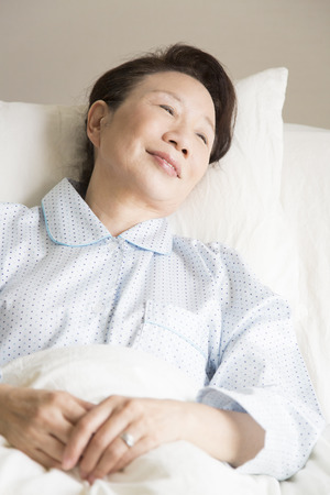 fostering: Senior woman to lie in bed Stock Photo