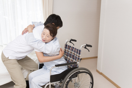 the elderly residence: Caregiver to put the senior woman in a wheelchair Stock Photo