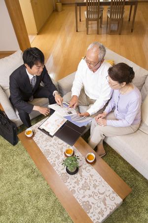 home life: Senior couple See salesman and brochure
