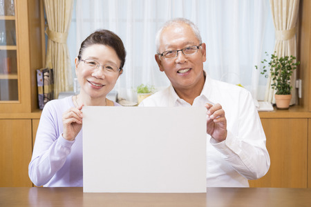 message board: Senior couple smiling with a message board Stock Photo