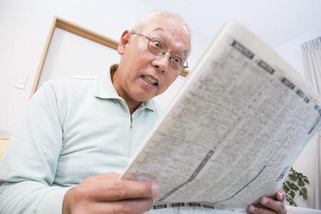 senior men: Senior surprised to read the newspaper man