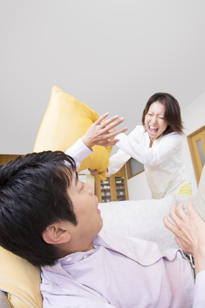 throw cushion: Wife throw the cushion to husband Stock Photo