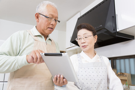 granny and grandad: Senior couple to cuisine while watching the tablet PC