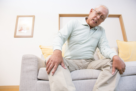 the elderly residence: Senior man suffering from pain in the knee Stock Photo