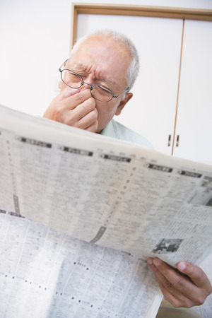 tired eyes: Senior man is tired eyes reading the newspaper Stock Photo