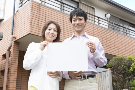 message board: Middle couple smiling with a message board