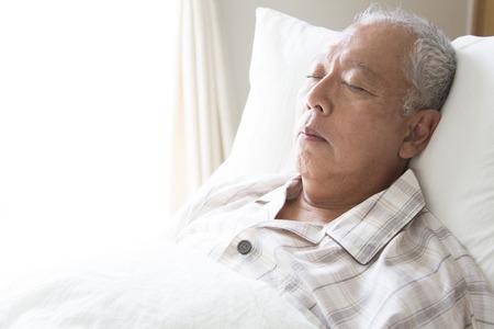 dormir: Hombres mayores que duermen en la cama Foto de archivo