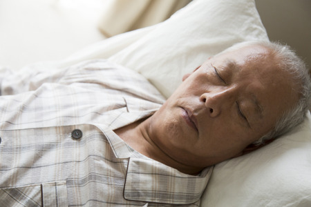 fostering: Hand of senior men who sleep in the nursing bed Stock Photo