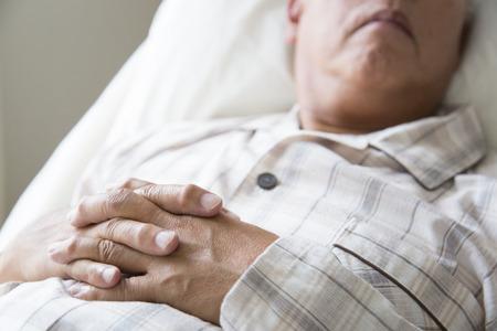 sixty: Hand of senior men who sleep in the nursing bed Stock Photo