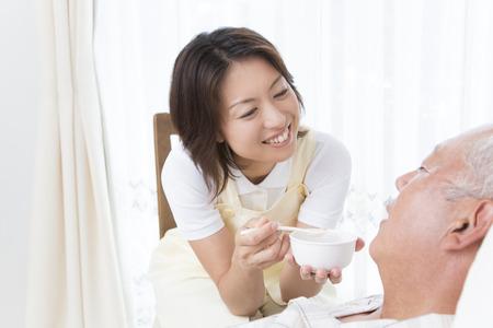 the elderly residence: Caregiver to feed porridge to senior men