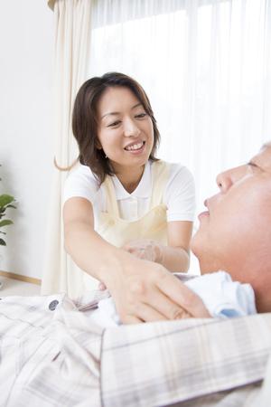 the elderly residence: Caregiver to wipe the body of senior men Stock Photo