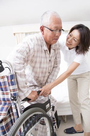 Senior homme tente de s'asseoir dans un fauteuil roulant