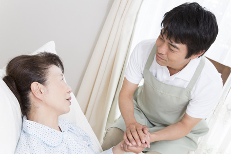 Caregiver holding the hand of a senior woman