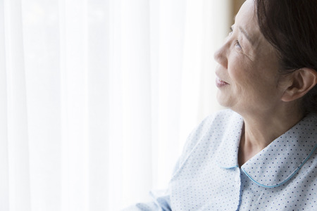 the elderly residence: Senior women stare out of the window
