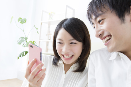 Couples laugh to see the smartphone