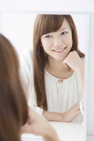 salubrious: Women smile and look in the mirror
