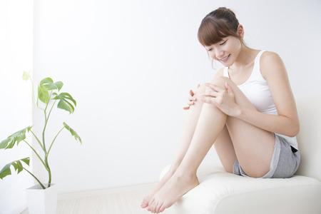 Žena se dotýká nohu Reklamní fotografie