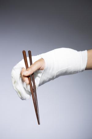 bandaged: Hands bandaged with chopsticks
