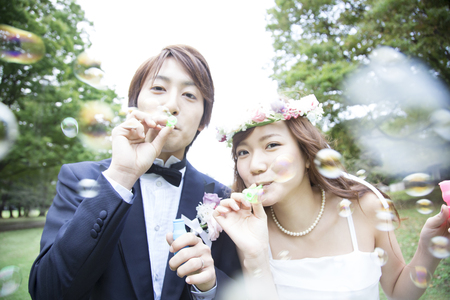 Bride and groom play with bubbles Stok Fotoğraf