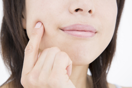 Women hold the cheek with a finger