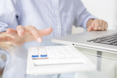 operate: Hand of the woman to operate the notebook PC and calculator Stock Photo