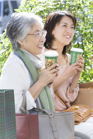 step daughter: Mother and daughter to rest on a bench Stock Photo
