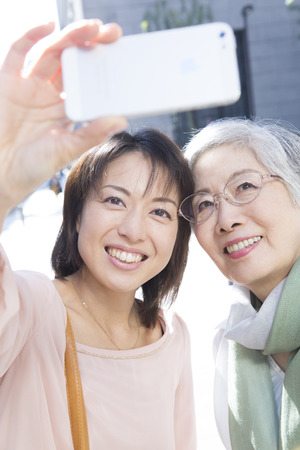 Take a commemorative photo in smart phones the mother and daughter