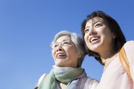 Bajo el cielo azul sonriendo madre e hija. Foto de archivo
