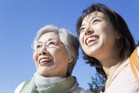 pleasent: Under the blue sky smiling mother and daughter. Stock Photo