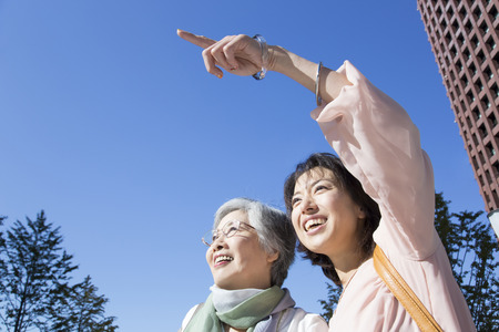 step daughter: Under the blue sky smiling mother and daughter. Stock Photo
