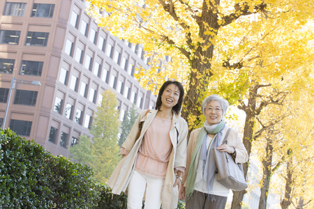 step daughter: Ginkgo treelined walk mother and daughter Stock Photo