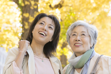 persona viajando: Mother and daughter smiling under the ginkgo tree-lined Foto de archivo