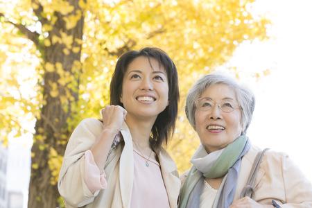 母と娘のイチョウ並木の下で笑顔