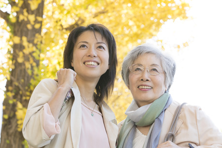 step daughter: Mother and daughter smiling under the ginkgo tree-lined Stock Photo