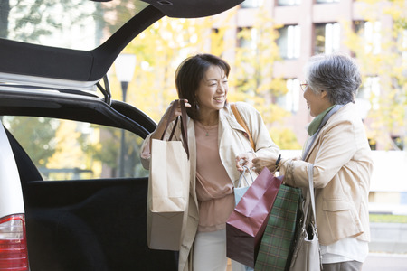 La madre y la hija de carga de equipaje en el coche Foto de archivo - 43795594