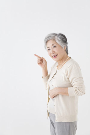 Senior woman to a finger-pointing Stock Photo