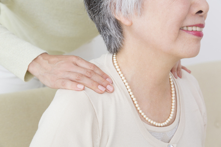 piety: Hand of daughter massage the mother of shoulder Stock Photo