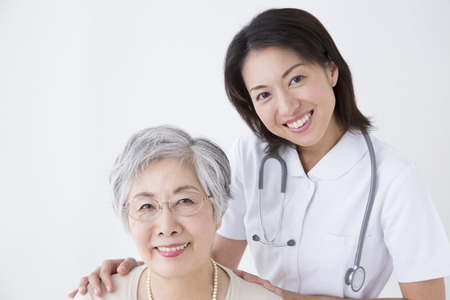 Hospital care: Smiling senior woman and nurse