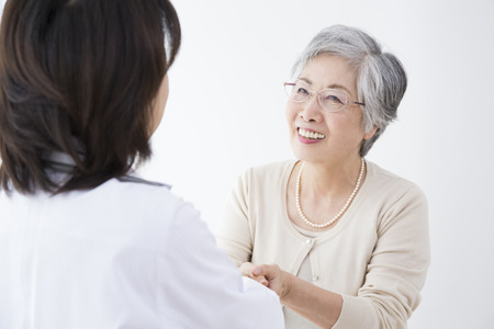 Senior women to shake hands with female doctor