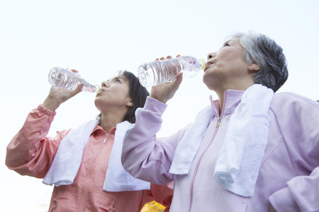 salubrious: Mother and daughter drinking water after exercise